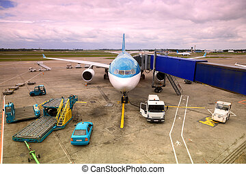 airliner with nonreal color parked at airport. boarding passengers tube. service technician