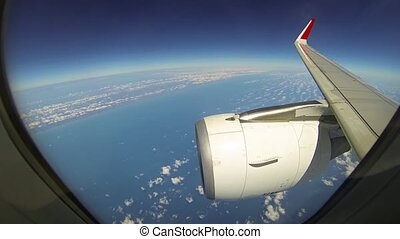 """""""Earth's Curvature is visible under the wingtip and engine cowling of an airliner, as seen through the passenger window at high altitude. Full HD video"""""""