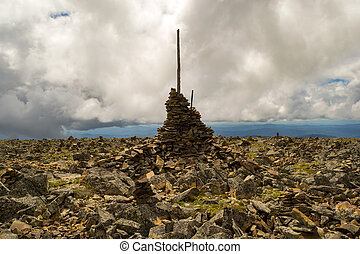 ?airn made up of each other on top of a mountain in Altai to indicate the path and the road for travelers not to get lost in the background of a large number of stones and large clouds in the sky
