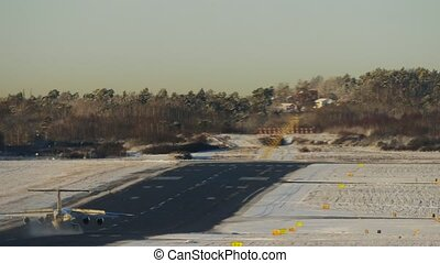 Airplaine in winter airport moving on a runway after landing and turning rigth to a taxiway. Heat haze over the plane