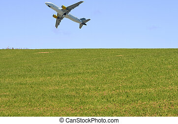 Airplane above grass - Airplane taking off in a blue sky...