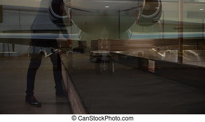Animation of airplane over businessman picking up suitcase from conveyor belt in the airport. Global travel holiday business concept digitally generated image.