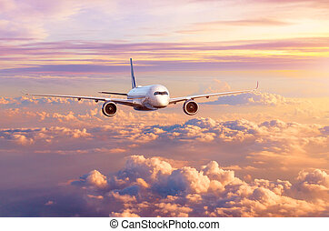 Airplane airliner flies over beautiful evening clouds, in the sky at sunset.