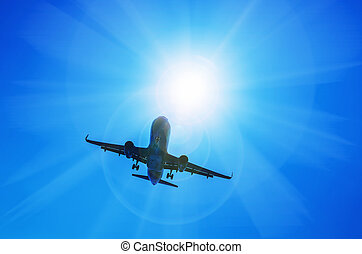 Airplane and sunbeam with lens flare effect on blue sky ...