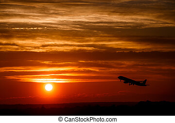 Airplane at sunset sky in the air with space for text. Silhouette of a big passenger  aircraft in sun light. transportation concept. plane flying in the dramatic sky. amazing atmospheric image