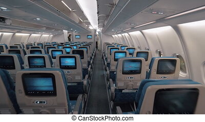 Airplane cabin with aisle and empty seats of economy class -...