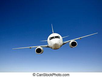 Airplane Flight - Airplane in flight against a bright blue...