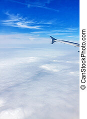 Airplane flight - window view over the clouds