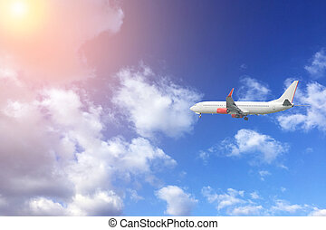 Airplane fly in the blue sky with sun.  Travel concept