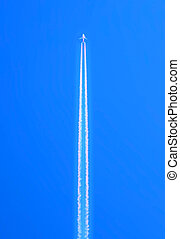Airplane flying at high altitude leaving its white wake over...