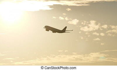 Airplane flying at sunset - Airplane gaining height after...