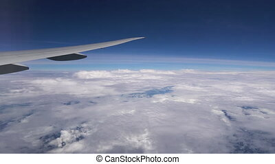 Airplane flying high in the clouds. Plane wing during flight