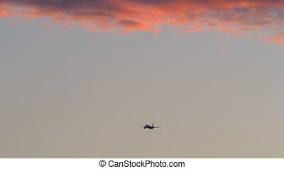 Airplane flying in evening sky with red clouds