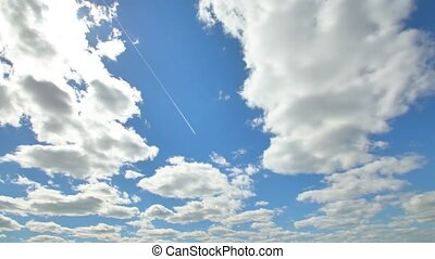 Airplane flying in the blue sky among clouds and sunlight.