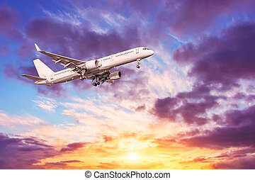 Airplane flying in the sky, near airport. Beautiful vibrant sunset sky with clouds of different tiers height various shades backlit by sunlight.