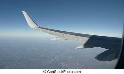 Wing of an airplane flying above the beautiful earth. -...