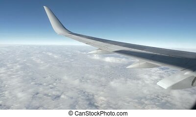Wing of an airplane flying above the beautiful white clouds....