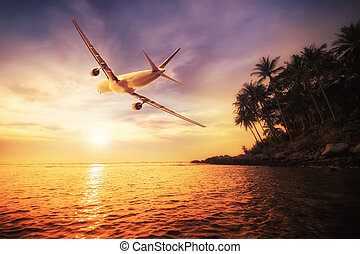 Airplane flying over amazing tropical sunset landscape