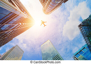 Airplane flying over modern business skyscrapers. Transport,...