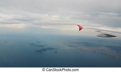 Airplane flying over the sea, view from the window - ...