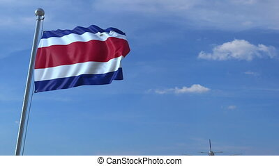 Airplane flying over waving flag of Costa Rica