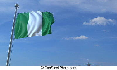 Airplane flying over waving flag of Nigeria