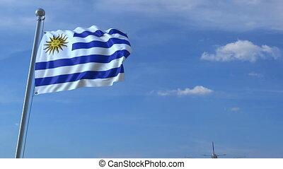 Airplane flying over waving flag of Uruguay