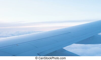 Airplane goes on landing, the view from the window to the wing of the aircraft and clouds