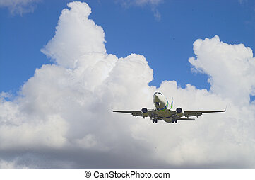 Airplane in a blue and white sky - Airplane landing with...
