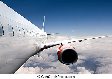 Airplane in flight - A airliner flies high over clouds
