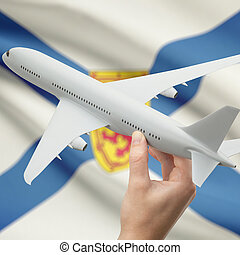 Airplane in hand with Canadian province flag on background - Nova Scotia