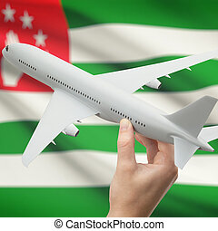 Airplane in hand with flag on background - Abkhazia
