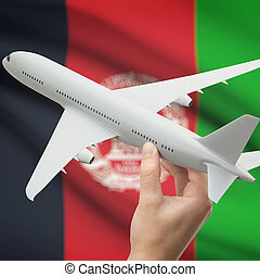 Airplane in hand with flag on background - Afghanistan