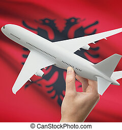 Airplane in hand with flag on background - Albania
