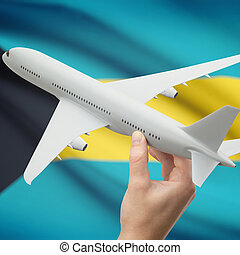 Airplane in hand with flag on background - Bahamas