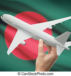 Airplane in hand with flag on background - Bangladesh