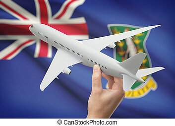 Airplane in hand with flag on background - British Virgin Islands