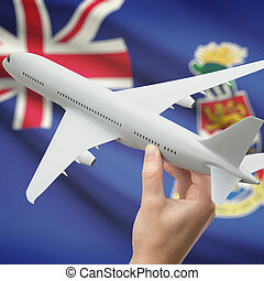 Airplane in hand with flag on background - Cayman Islands
