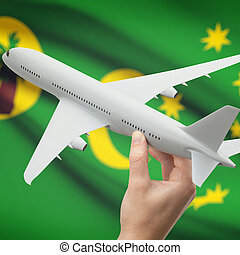 Airplane in hand with flag on background - Cocos (Keeling) Islands