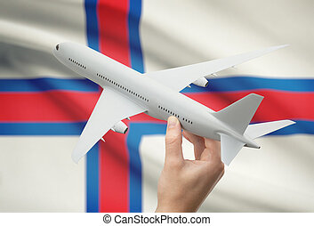Airplane in hand with flag on background - Faroe Islands