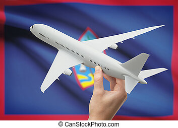 Airplane in hand with flag on background - Guam