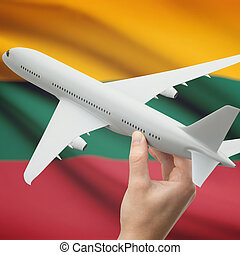 Airplane in hand with flag on background - Lithuania