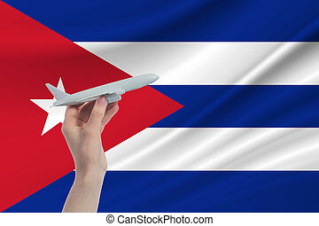 Airplane in hand with national flag of Cuba Travel to Cuba