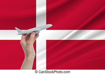 Airplane in hand with national flag of Denmark. Travel to Denmark