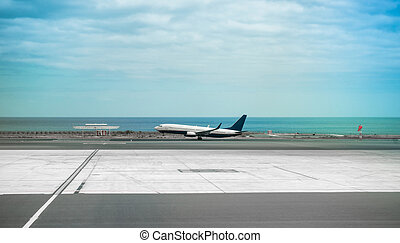 airplane in Lanzarote airport runaway with sea on the background