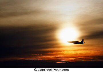 Airplane in the air at sunset  background with space for text. Silhouette of a big passenger or cargo aircraft in sun light. transportation concept. plane flying in the sky. amazing image