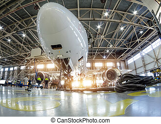 Airplane in the hangar for maintenance, bottom nose view.
