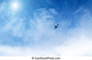 Airplane in the sky on a background of blue sky and white clouds.