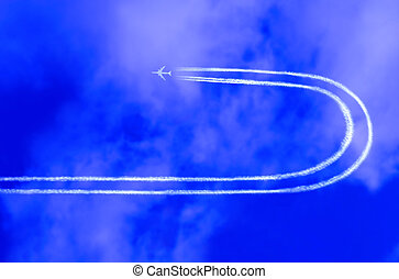 Airplane in the sky with jet trail making a u-turn