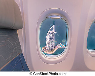 Airplane interior with window view of Burj Al Arab hotel, Dubai.